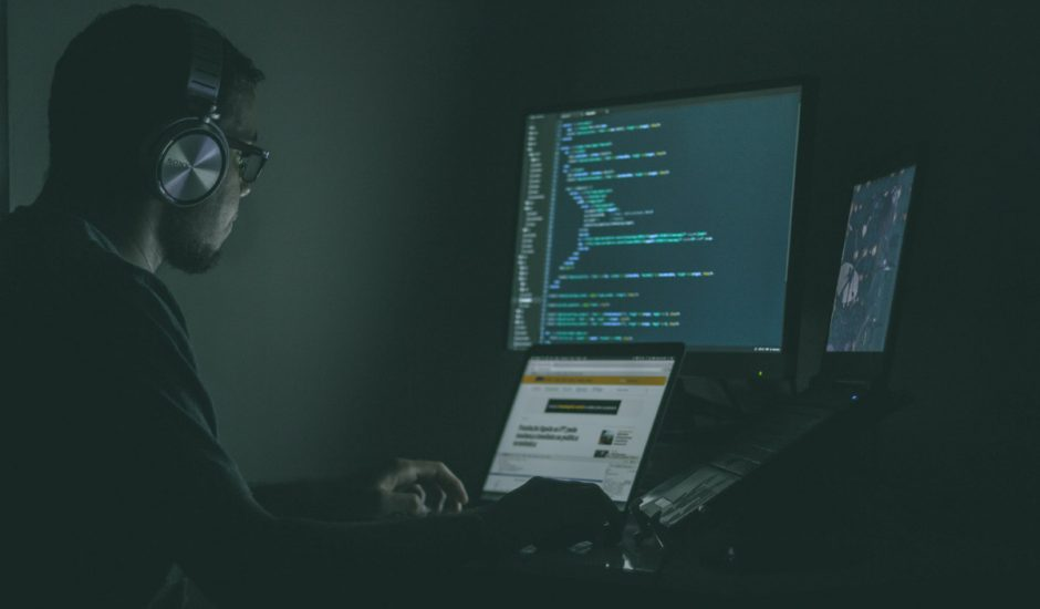 Un chercheur en cybersécurité travaille à son bureau face à plusieurs écrans