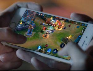 le jeu Honor of kings sur un téléphone joué par un jeune homme